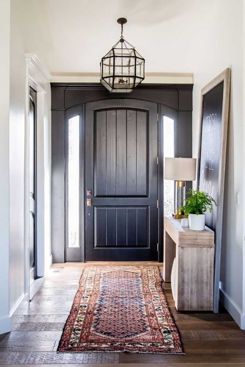 The entry with furniture and a lamp table and the ceiling light with the Kilim rug.