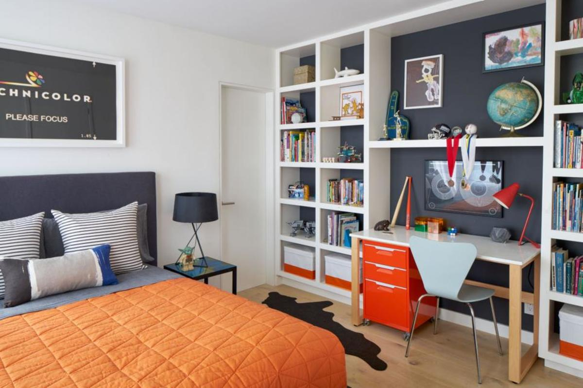 A teen's wall is storage with games,  toys, books with a desk, a filing cabinet and plenty of shelving.