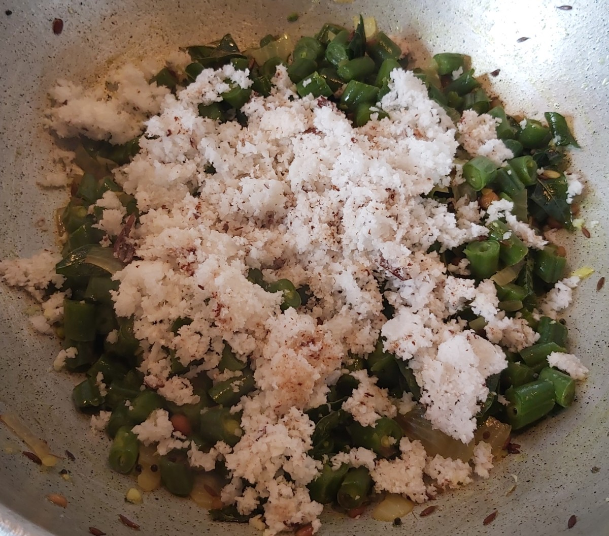 Add fresh grated coconut to cooked beans.
