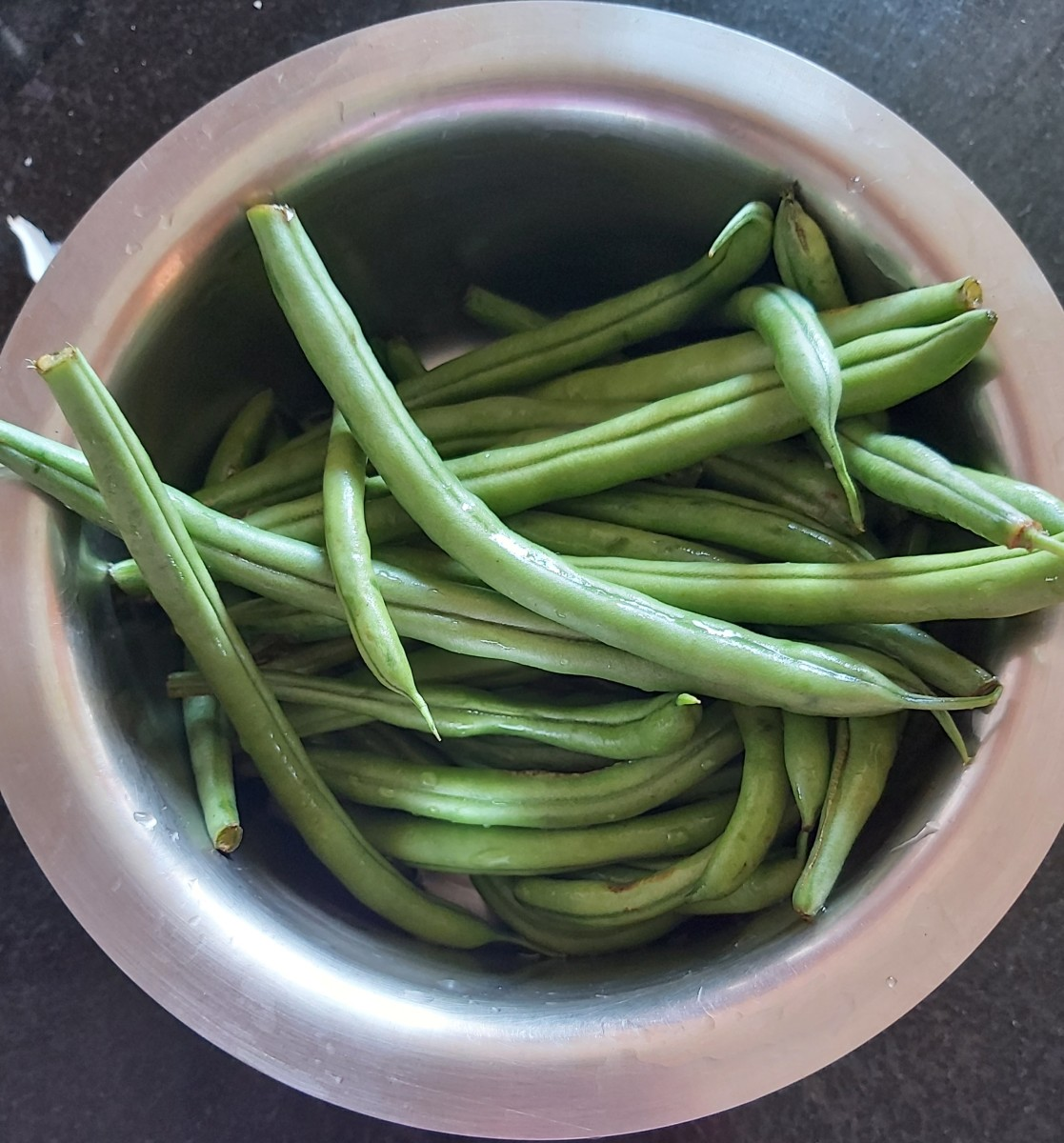 Wash and trim the French beans. Remove the fibrous strings if any.