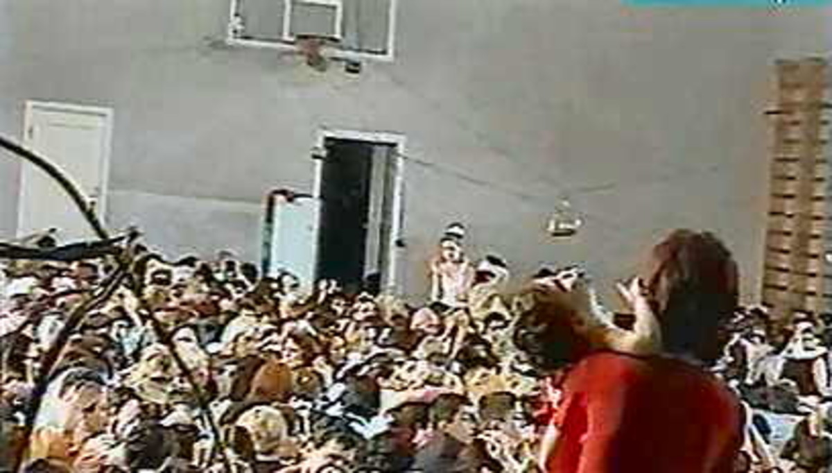 A view inside the gym, people packed in shoulder to shoulder, bombs visible strung between the basketball hoops