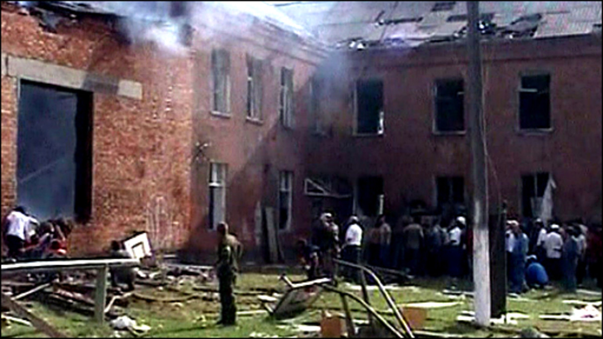 The burning schoolhouse after the siege was lifted, and civilians eagerly awaiting news of their loved ones.