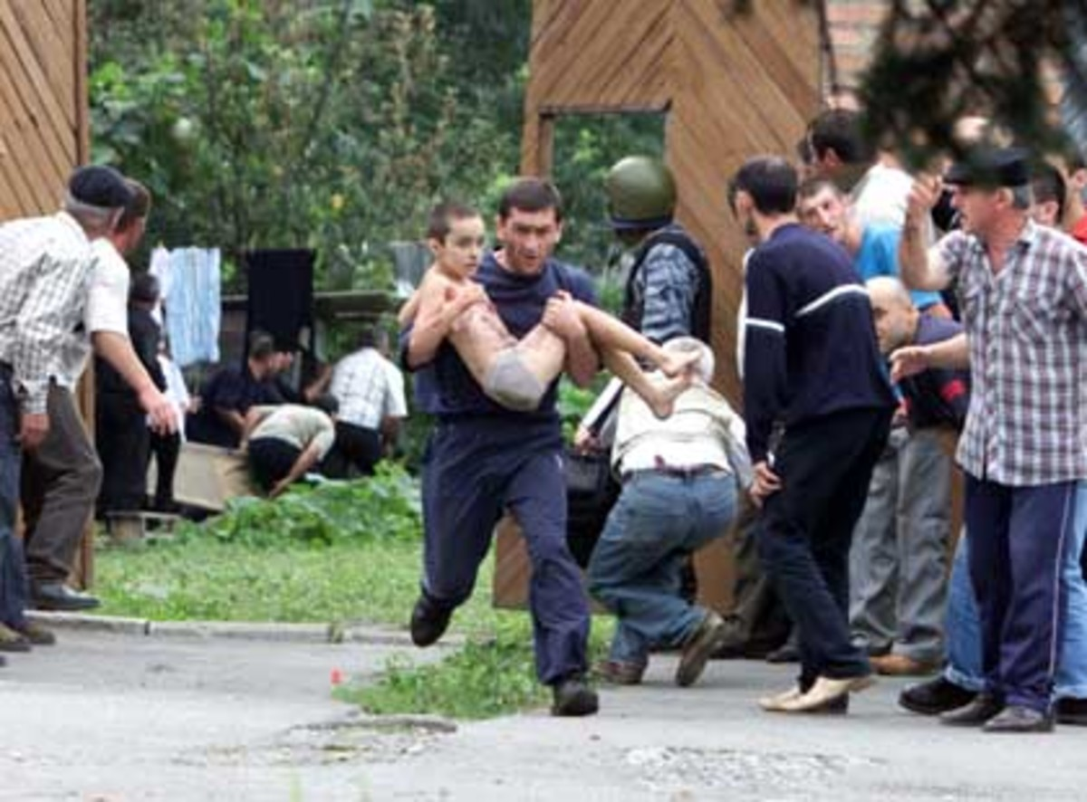 Unknown person rushing a child out of harm's way in Beslan school siege