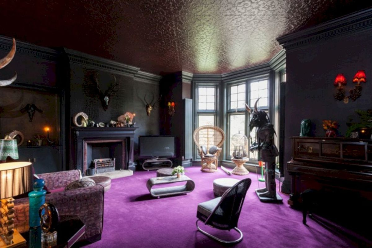 The Scorpio living room: a purple-blue carpet, rounded furniture, items in black and gray, gothic elements, and an inviting fireplace.