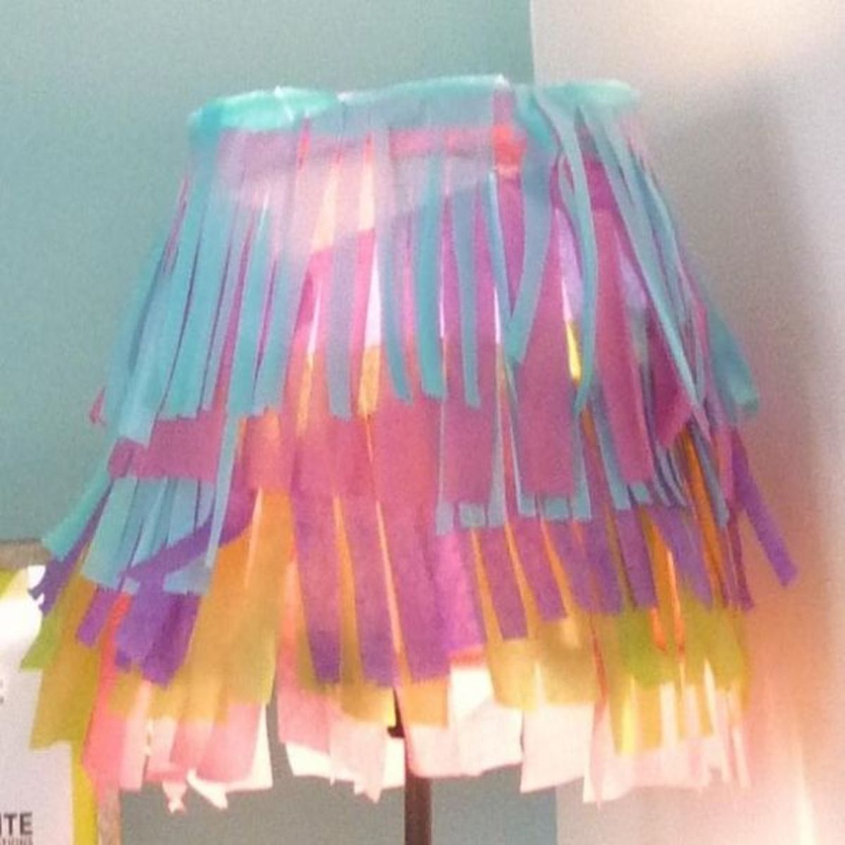 Embellish a white lampshade with rows of colored tissue paper cut into fringed lengths.  Layer the tissue paper to achieve a petticoat effect.