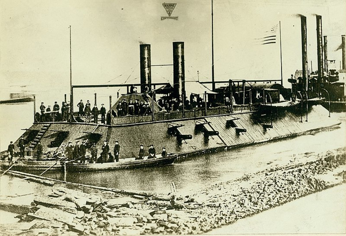 Photograph of an USS Cairo ironclad gunboat with sailors onboard. Two smaller rowboats are in the foreground with more sailors in them. In the background are other riverboats whose smoke stacks are visible.