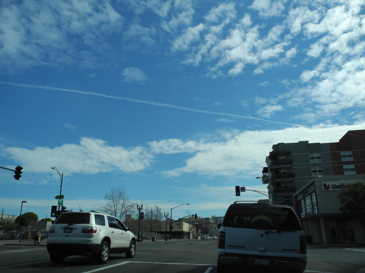Pencil Thin Chemtrail Line placed among already existing Chemtrail Clouds which were dispersing into Key Hole Punch Clouds. Downtown San Diego... with the same key hole punch type Swiss Cheese Clouds in other pics.