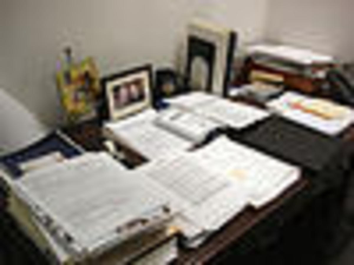 An example of a messy small writing desk - displays one of the potential drawbacks of a small office desk.