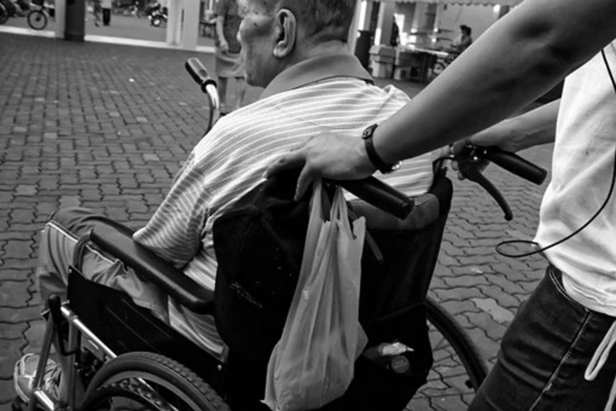 A caregiver assisting a wheelchair patient