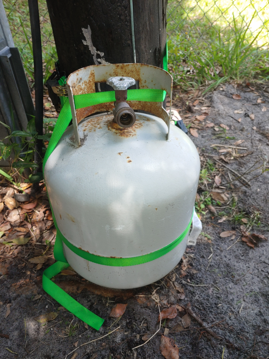Using Tie-down straps, attach your propane tank to a power line pole.