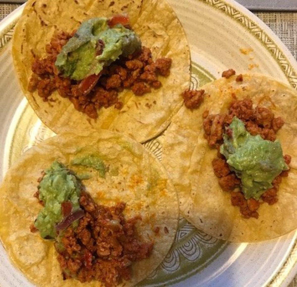 Al pastor tacos dolloped with delicious guacamole.