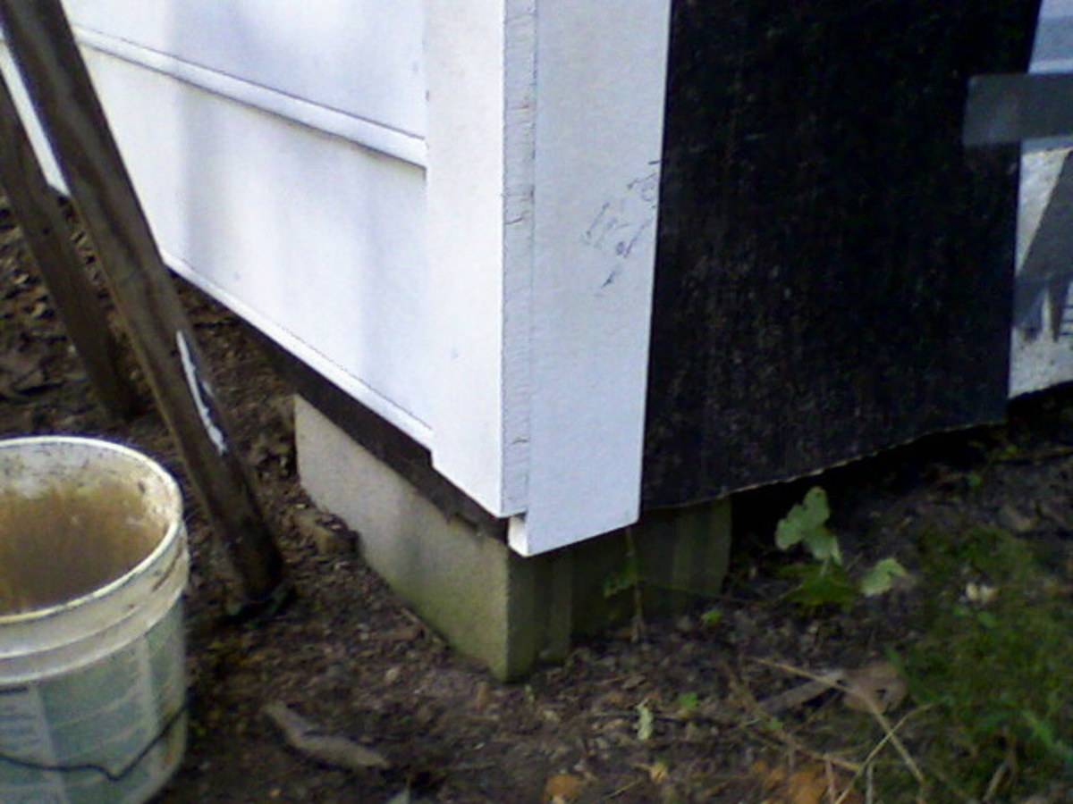 Detail of corner.  The Harditrim boards will be cut off evenly at the bottom; you may be able to avoid this step by careful measuring.  Note also the duct tape temporarily securing the tar paper.