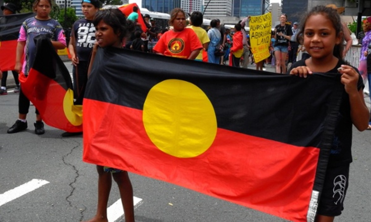 Children carrying the Australian Aboriginal Flag in Brisbane on Australia day.