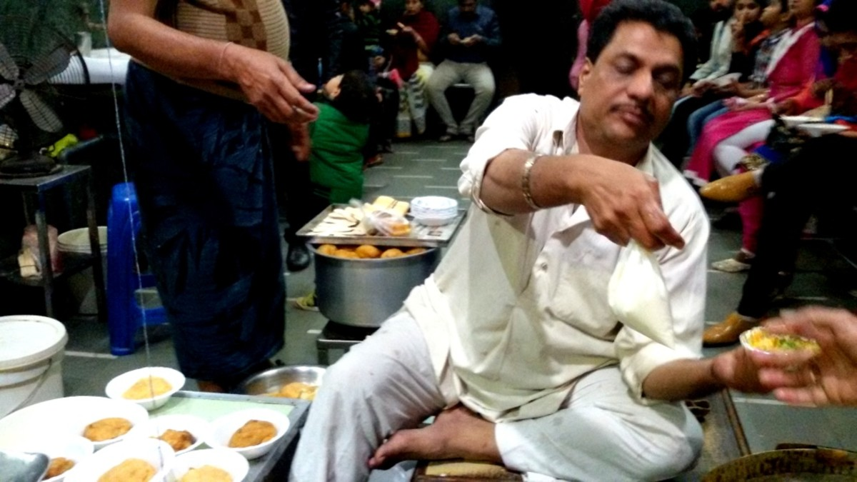 The person performing a conjurer's trick while preparing 'Dahi Badaa'-s at Joshi Dahi Badaa Stall