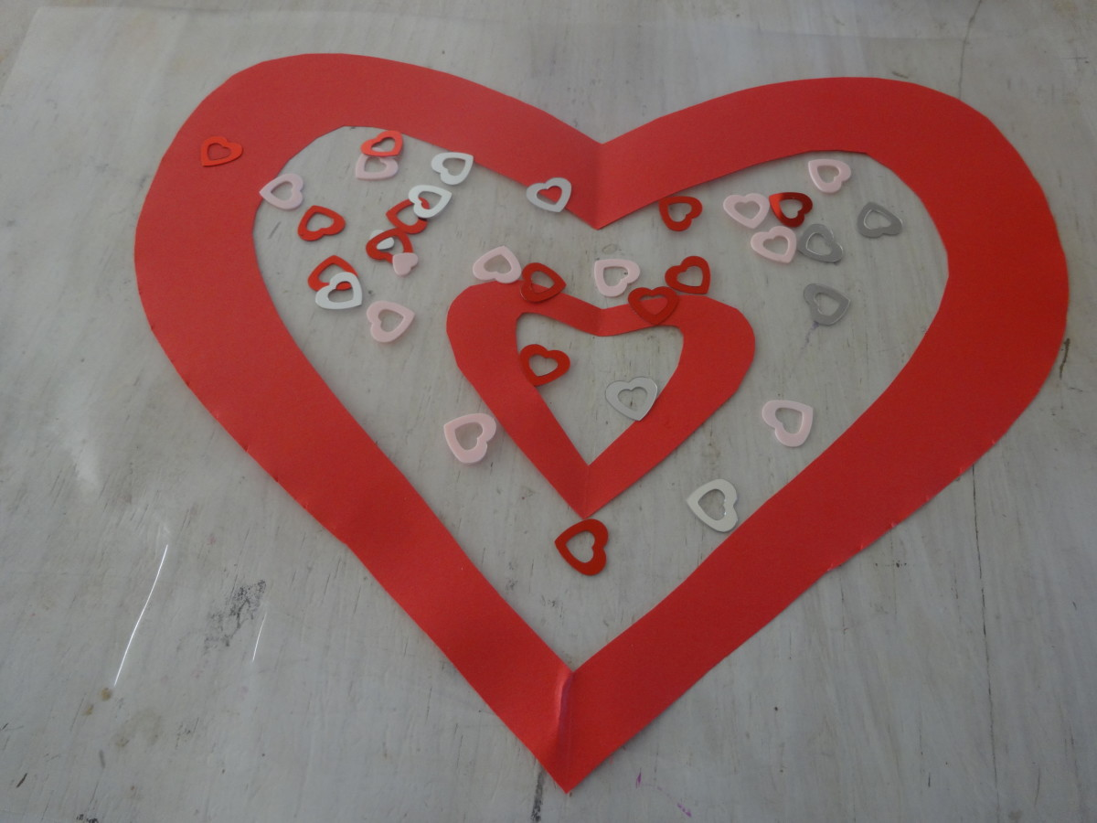 Lay the piece of contact paper on the surface sticky side up and lay the heart shape and a smaller heart and/or any other decorations on it.