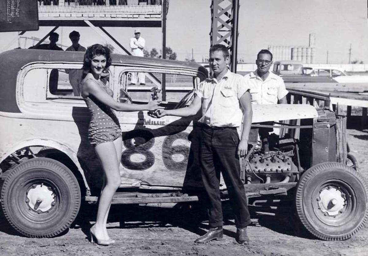 """Wilbur """"Willie"""" Berger of Newton, Kansas is shown here receiving the trophy that he was presented for winning the trophy dash at the Kansas State Fairgrounds, Labor Day 1957."""