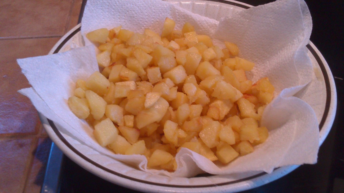 fried potatoes put on a lined bowl with kitchen paper to soak up excess cooking oil