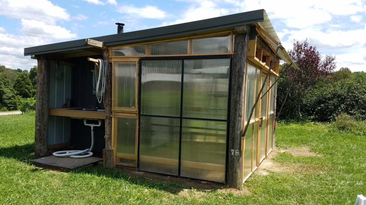 This multi-purpose garden shed combines a greenhouse, dehydrating shed, and outdoor kitchen into one building.