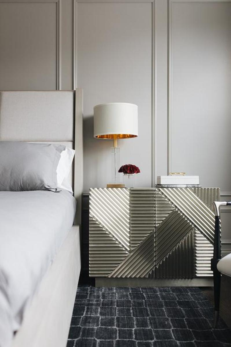 The bed wingback upholstered is the silver nightstand with the gold lamp. The rug is the gray wainscoted wall and the bedding gray sheets and comforter.