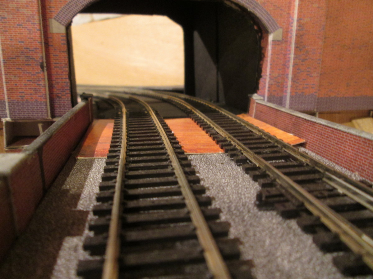 Off the layout and into Unit 7 fiddleyard through the baffle - added on the curve to simulate the entrance to a short tunnel and give the eye a sense of continuity instead of a jarring scenery break
