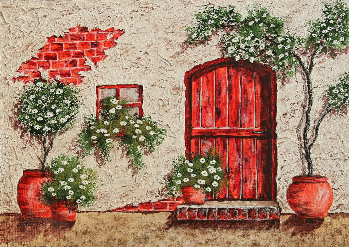 A red door entry to a country cottage framed with greenery in red planter pots on either side of the door.