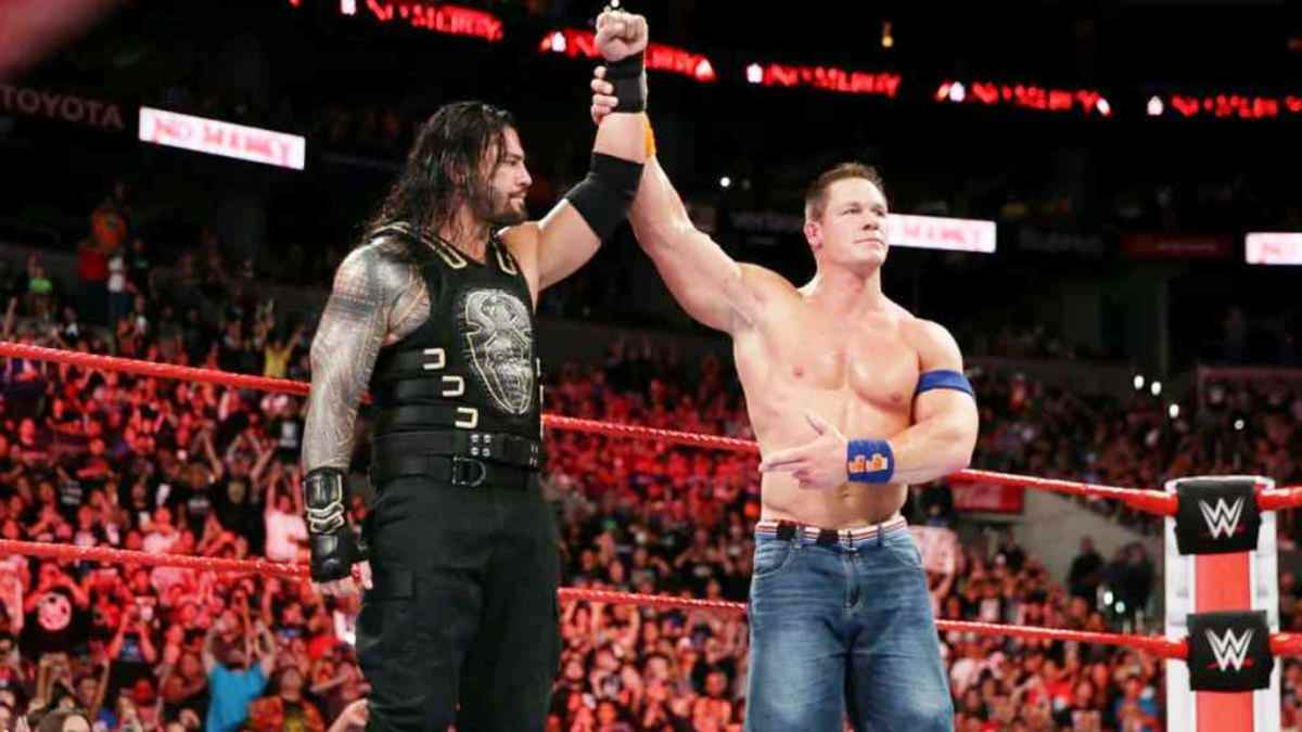 In a true show of sportsmanship, John Cena raises Roman Reigns' hand after their match.