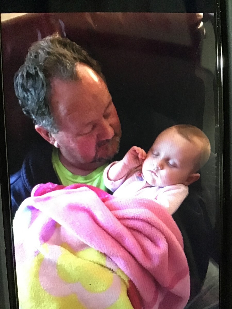 My dad holding our second daughter and putting her to sleep.