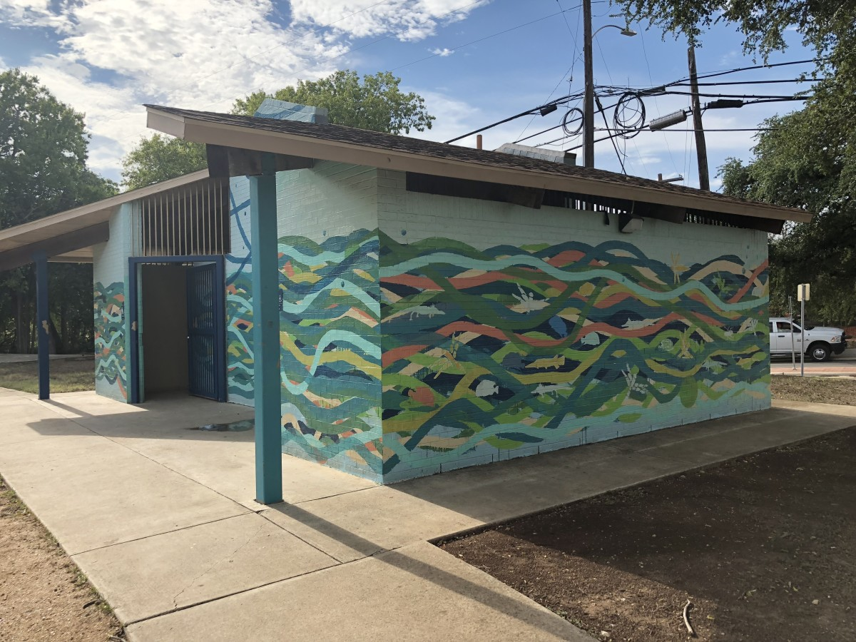 This mural depicts wildlife and swimmers in a river setting.