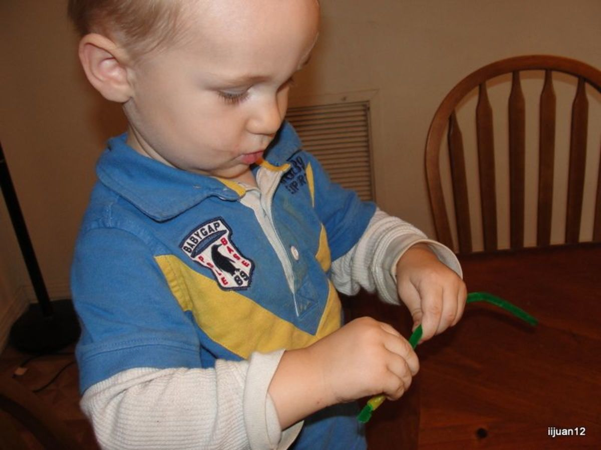 Stringing Cheerios onto pipe cleaners during toddler time