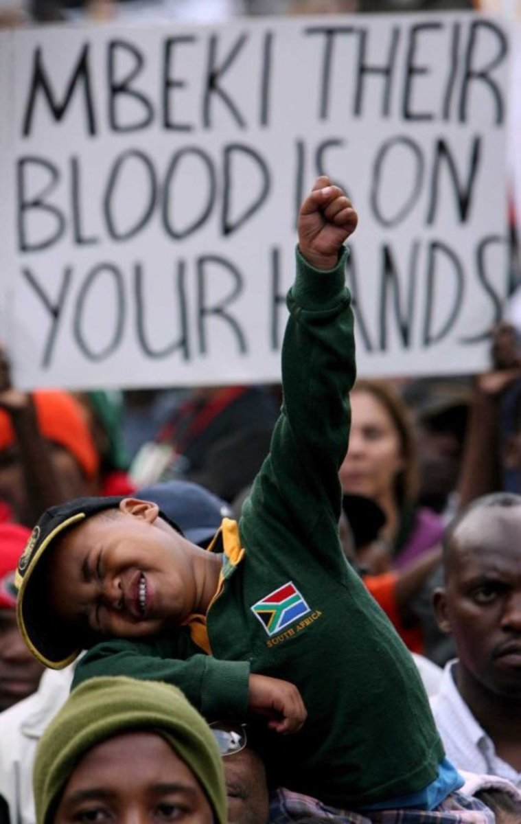 President Mbeki under placard and protestors attack for dragging the country under and exacerbating the AIDS pandemic. A Kid Encapsulates the fighting spirit of the African people in this picture