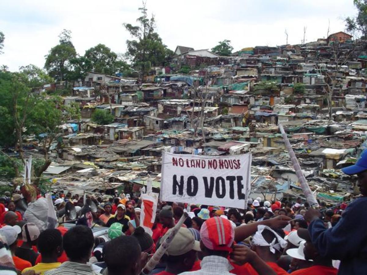 "Abahlali baseMjondolo, holding a rally, and the shack dwellers ramshackle houses in the background, and they were holding a sign that read: ""No Land! No Houses! No Vote"