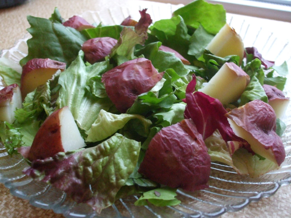 An inviting salad of mixed greens with chunks of chilled baked red potato.