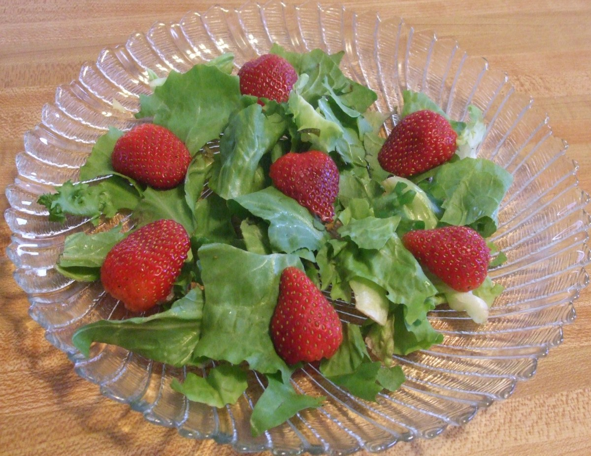 Strawberry halves on salad greens.