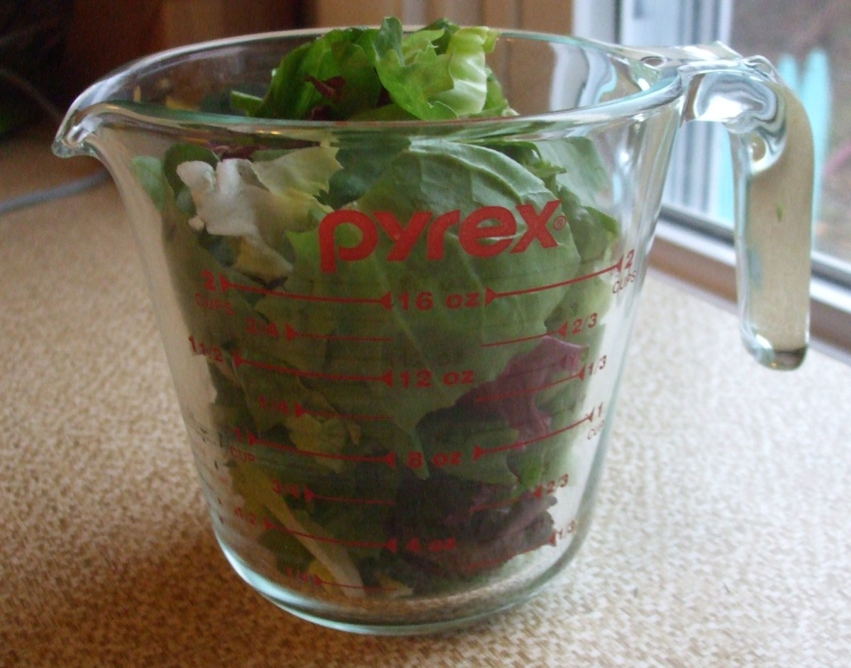 Two  cups of salad greens in a glass measuring cup.