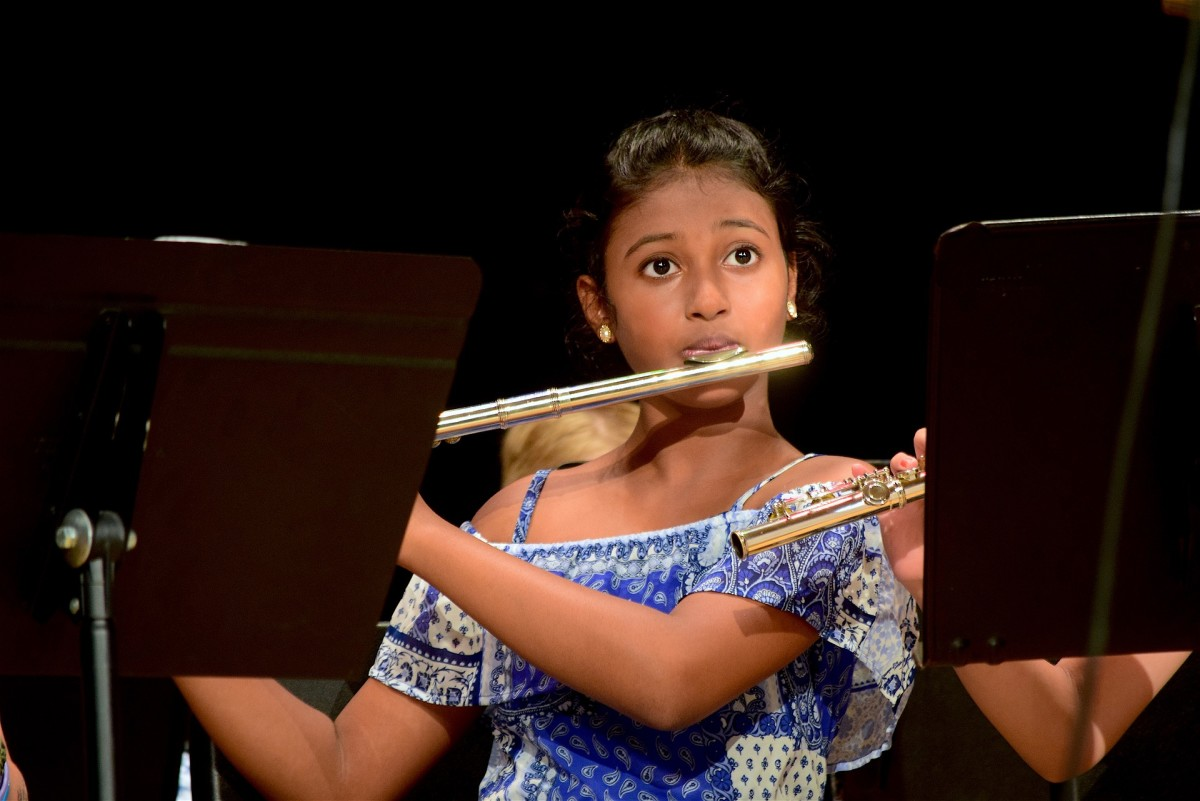 A young girl playing a flute.