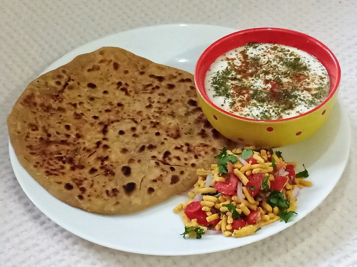 Sev paratha is crisp, spicy, and tangy. Served here with yoghurt sprinkled with some mint powder, roasted ground cumin seeds, red chilli powder, black pepper powder and the sev mixture made with sev, chopped onion, tomato, and cilantro.
