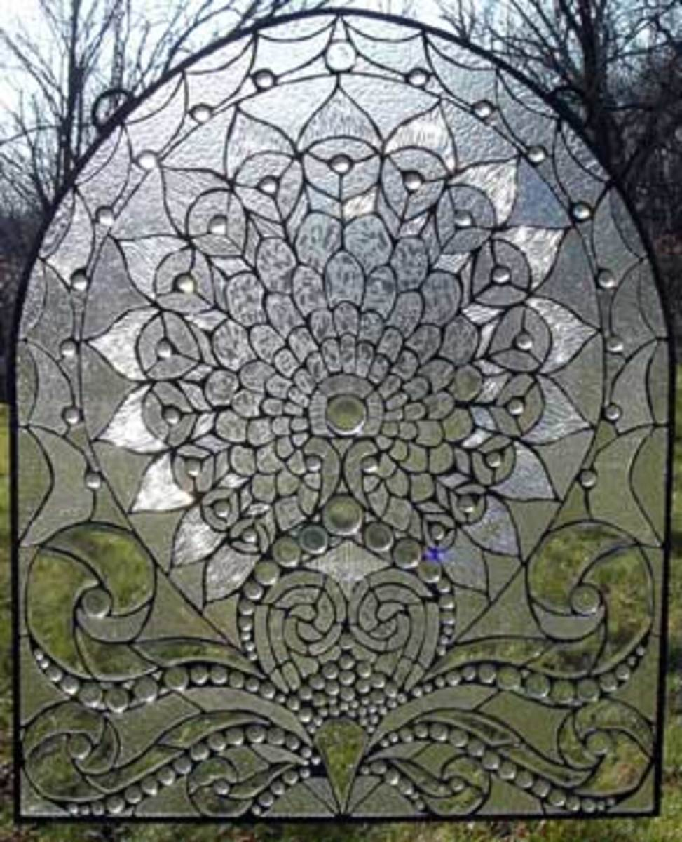 This stained glass panel has black lines surrounding each glass piece. That is due to the black patina which makes the colors stand out.