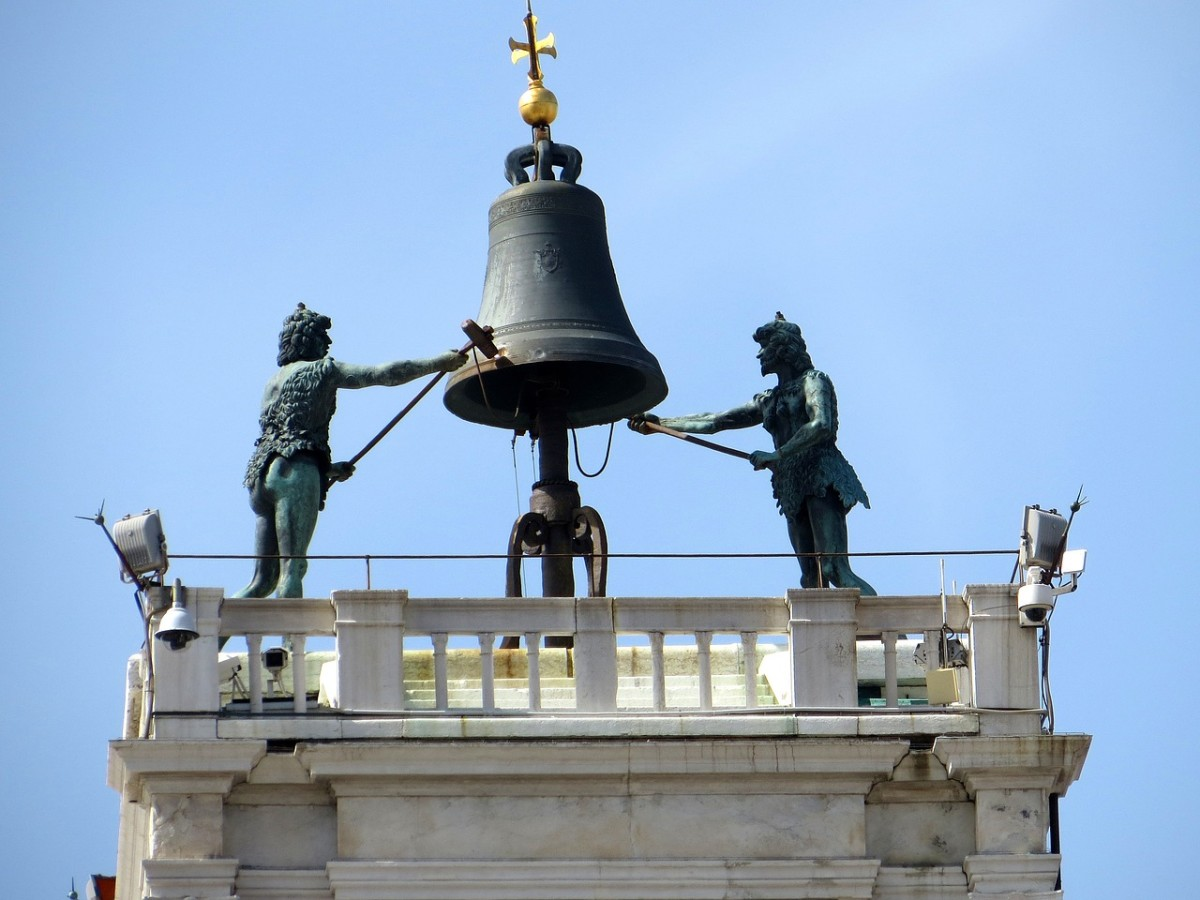 A close up of the statues and the bell on the clock tower.