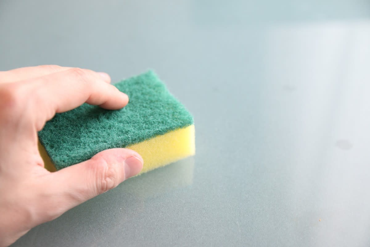 Person cleaning with a sponge