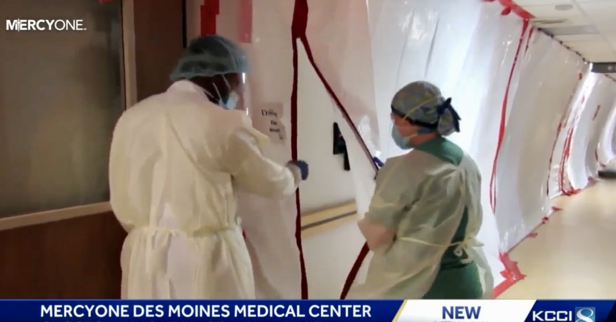 Nurse opens containment lock for doctor.