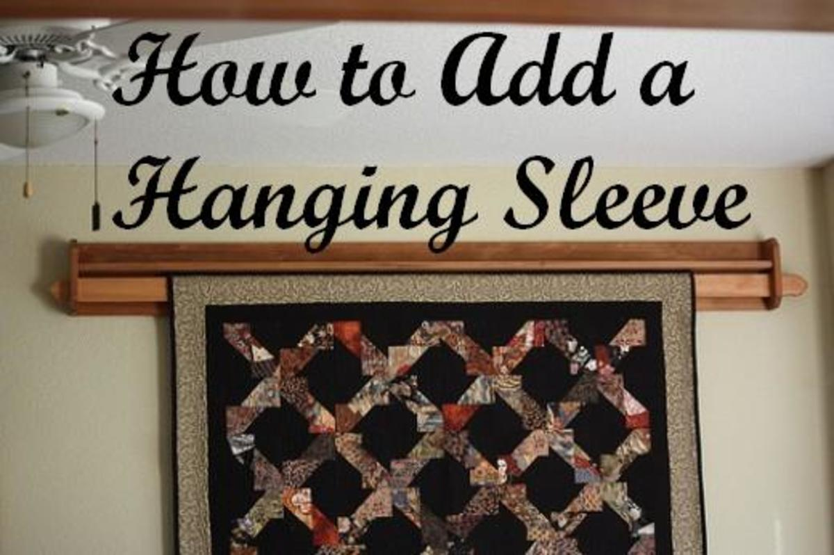 With this quilt holder, a piece of wood is inserted in the hanging sleeve and placed on the hanger that is attached to the wall.