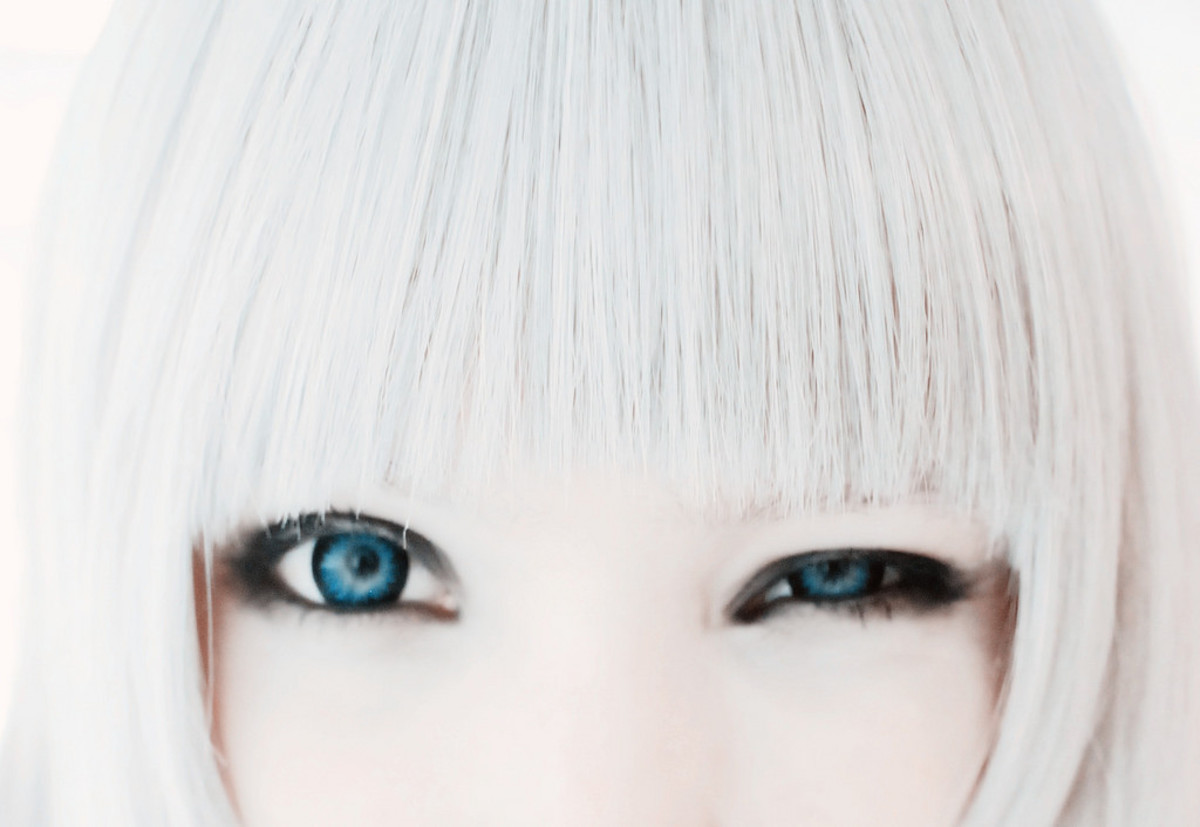 Closeup of woman's eyes and her silvery-white blunt cut bangs.