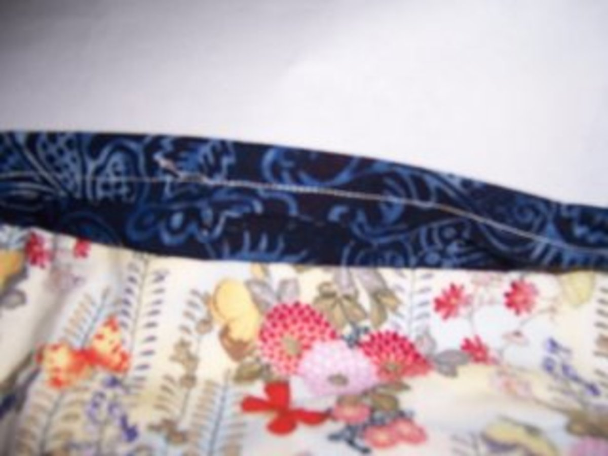 Create a tube of fabric with the seam allowance on the outside. Press and line up to the top of the back of the quilt.