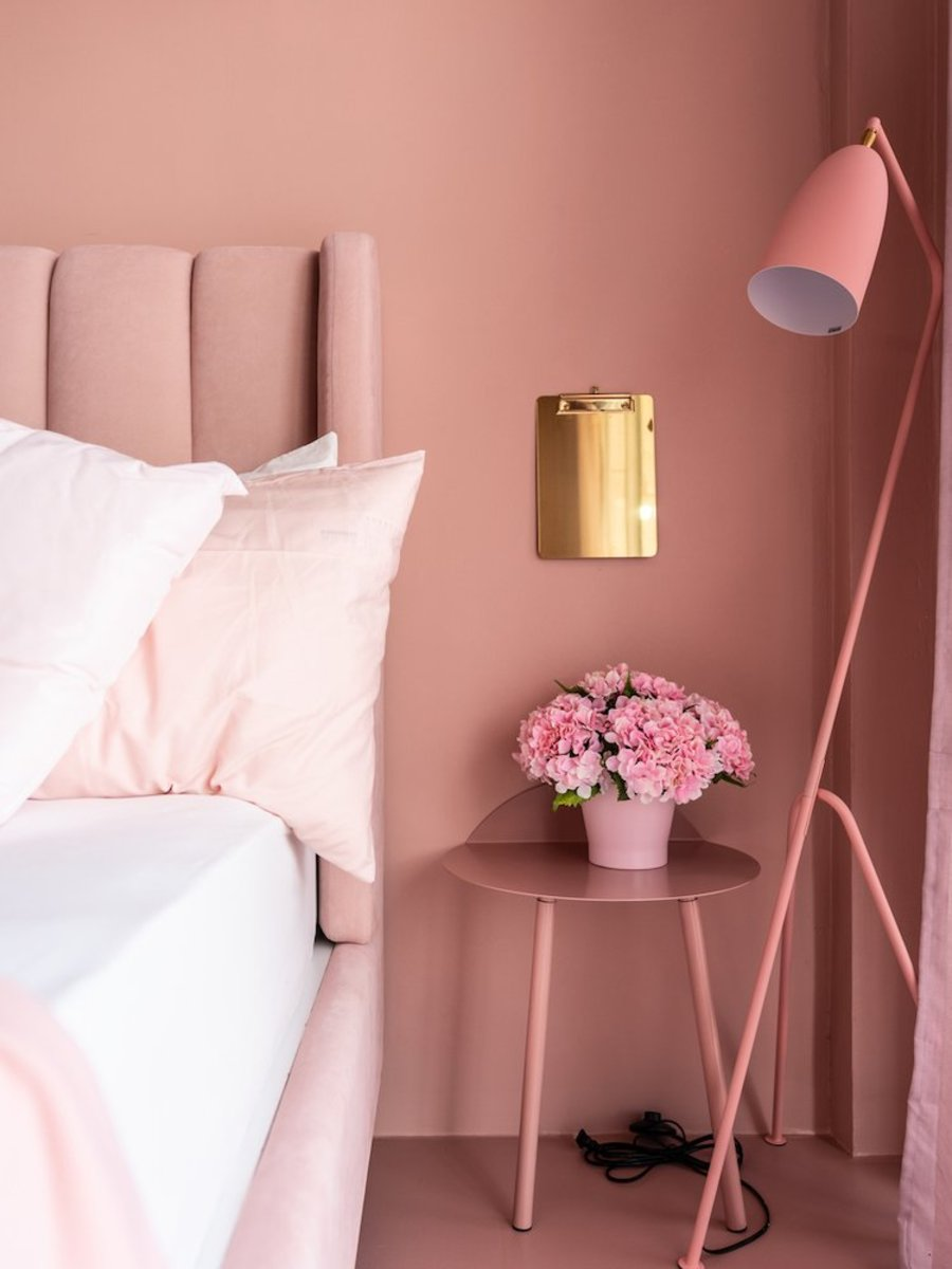 This the paint aged-pink wall is her teen bedroom that has monochrome furnitures.