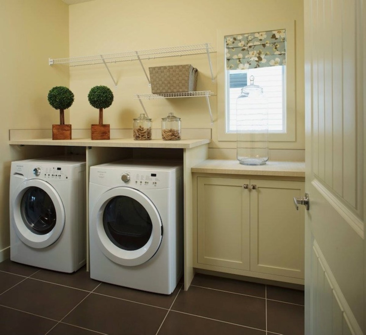 Lovely pale yellow laundry room with cream cabinetry with white laminate countertops and the white front-load washer and dryer.