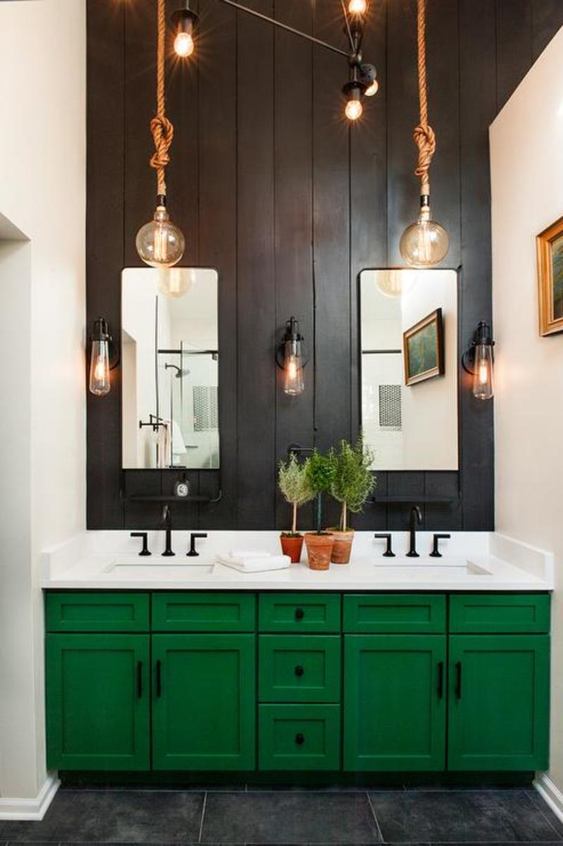 The vanity with emerald green paint and black on the wall. The top white counter and oil-bronze hardware.