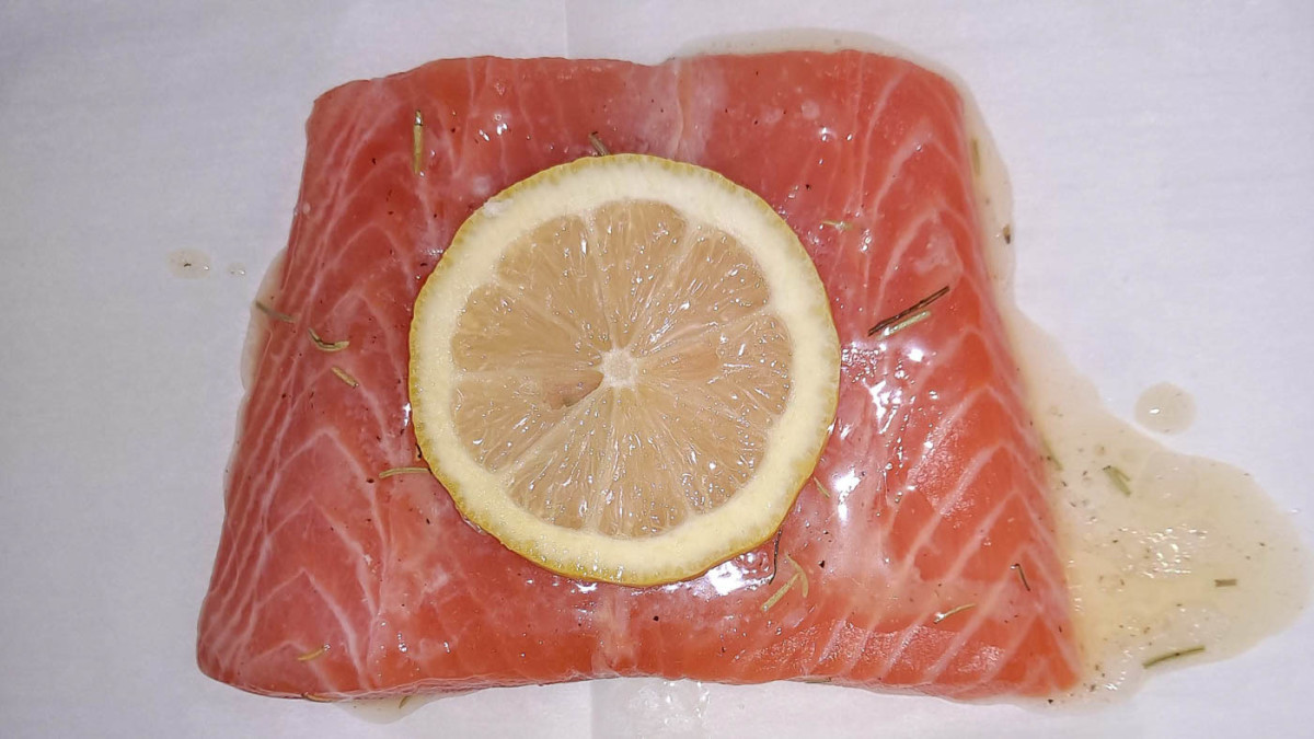 Glaze each salmon fillet with lemon butter sauce and then place a lemon slice on top. Now it's ready to bake.