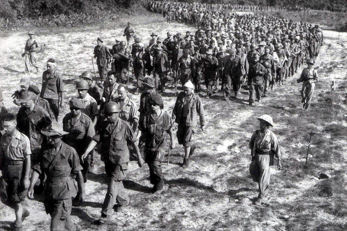 Captured French soldiers from the battle of Dien Bien Phu, escorted by Vietnamese troops, walk to a prisoner-of-war camp