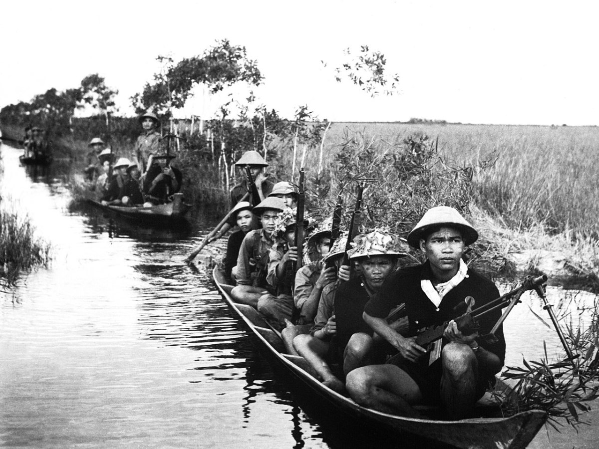 Viet Cong fighters crossing a river in the Mekong Delta region of South Vietnam.