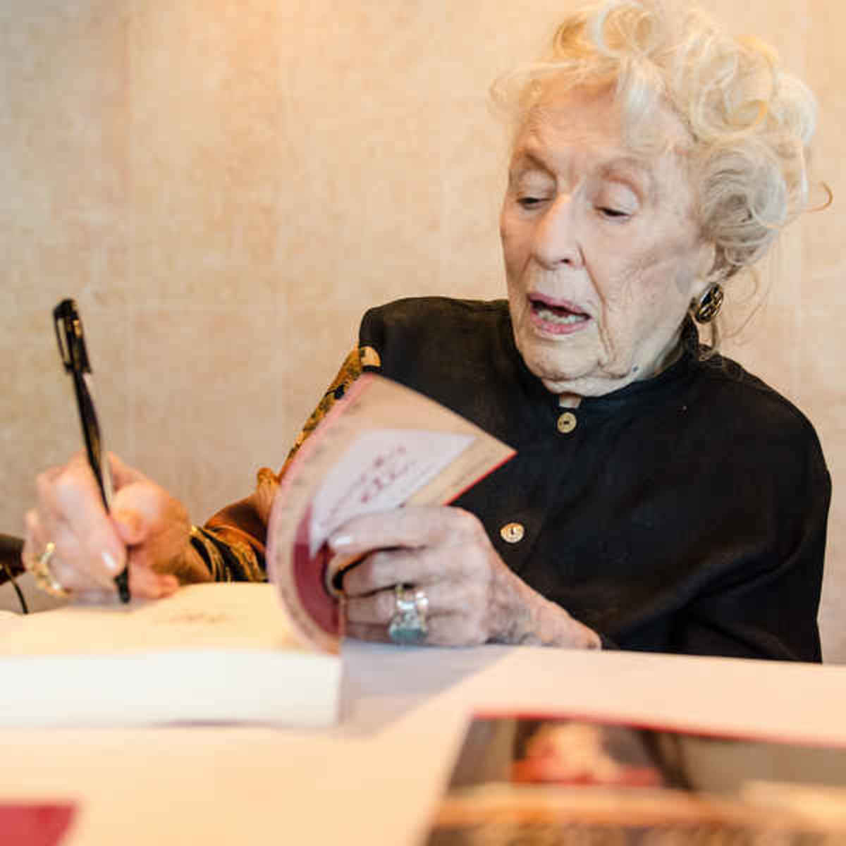 "Her book was released as an ebook, and Bel said she enjoyed signing ""paper copies"" of her book. She is 102 in this photo."